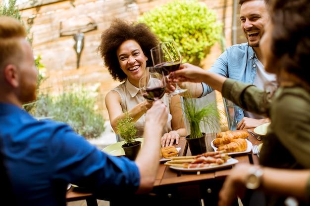 Jovens alegres almoçar no pátio e brindar com vinho tinto