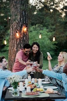 Jovens alegres amigos de várias etnias sentados ao lado de uma mesa festiva sob um pinheiro e batendo copos de vinho tinto na festa