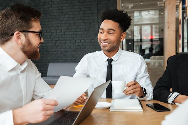 Jovens alegres colegas dentro de coworking