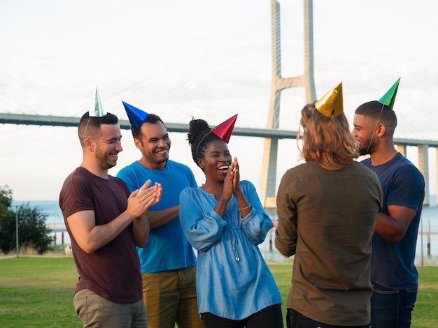 Jovens alegres fazendo surpresa para seu amigo. bons amigos dando presentes para mulher jovem e feliz. conceito de surpresa de aniversário
