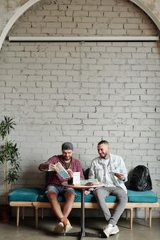 Jovens alegres sentados à mesa em um café moderno com design de loft e discutindo a rota da viagem enquanto planejam as férias juntos