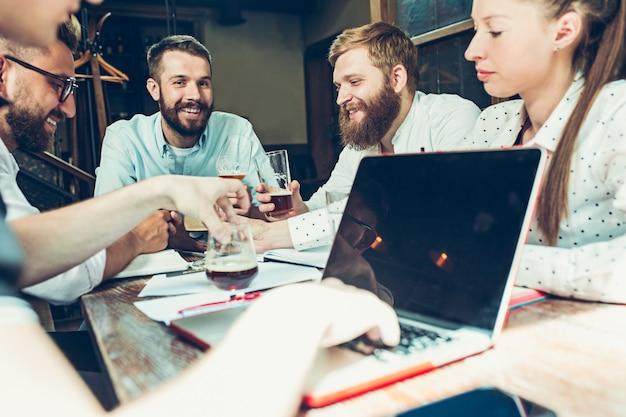 Jovens alegres sorriam e gesticulam enquanto relaxa no pub