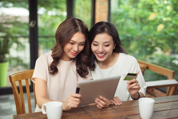 Jovens alegres usando tablet digital, comprando on-line com cartão de crédito em uma cafeteria