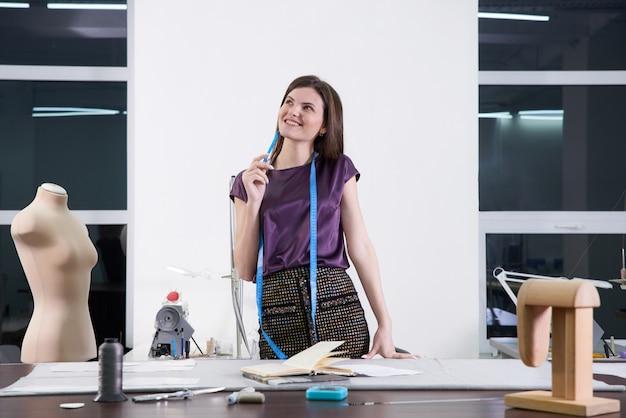 Jovens alfaiate em sua oficina de design de roupas novas, atelier studio
