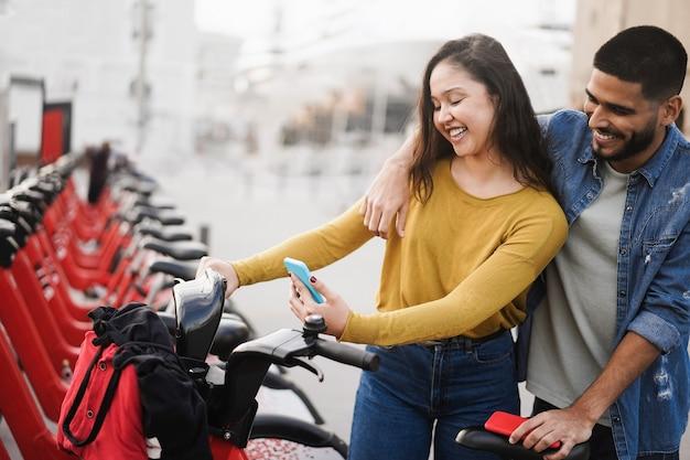 Jovens alugando bicicleta elétrica com app para smartphone