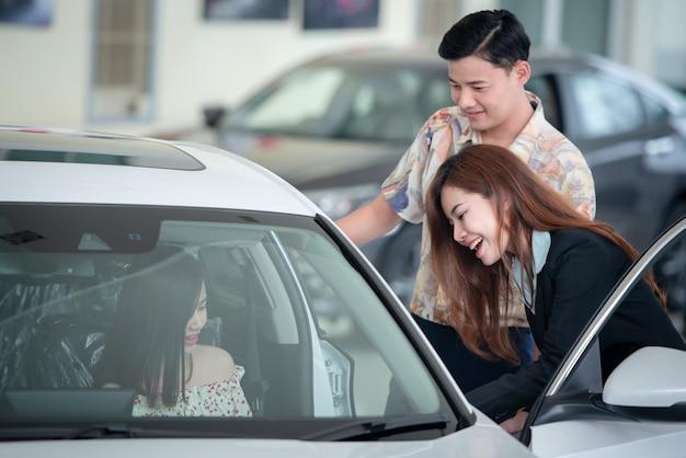 Jovens amantes asiáticos ficam felizes em comprar um carro novo no revendedor e comprar um carro com o revendedor.