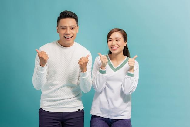 Jovens amantes atraentes e alegres mostrando o polegar para cima