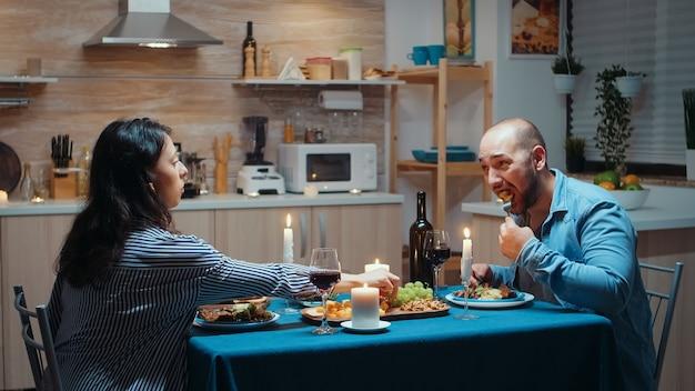 Jovens amantes comendo comida saudável no jantar. casal feliz conversando, sentado à mesa na sala de jantar, apreciando a refeição, comemorando seu aniversário em casa tendo um tempo romântico.