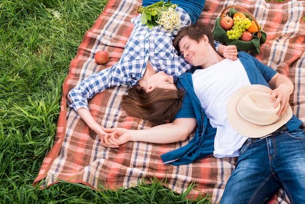 Jovens amantes deitado no xadrez na floresta