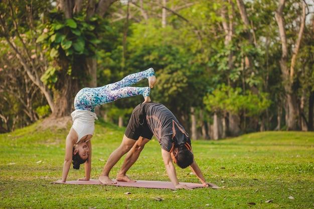 Jovens amantes do yoga fazendo acrobacias