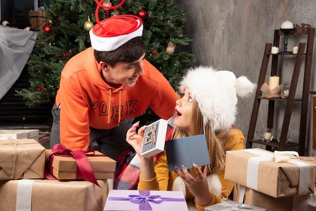 Jovens amantes felizes olhando para os presentes de natal na sala de estar.