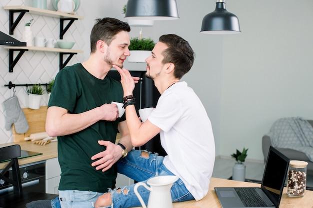 Jovens amantes homossexuais se olhando em casa. casal gay sorridente feliz tomando café juntos na cozinha