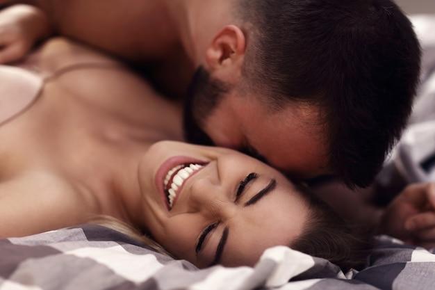 Jovens amantes sensuais sendo íntimos na cama
