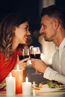 Jovens amantes sorridentes, olhando um para o outro e jantar romântico com vinho e comida
