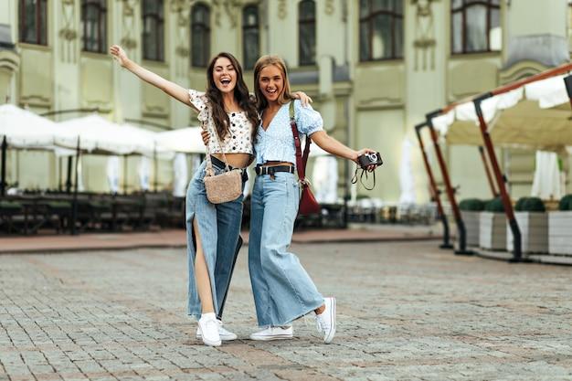 Jovens amigas bronzeadas e descoladas em jeans soltos da moda e blusas florais se abraçam ao ar livre