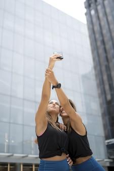 Jovens amigas caminhando perto de edifícios e tirando selfies durante o dia