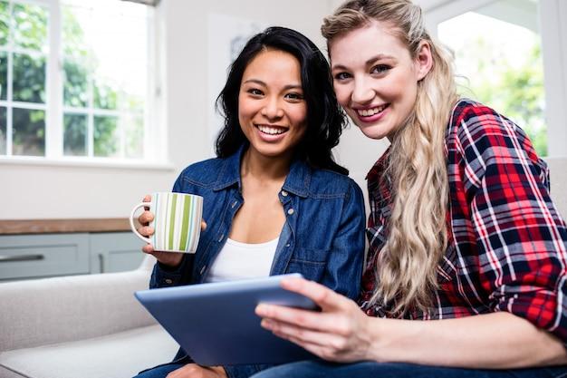Jovens amigas com copo e tablet digital no sofá