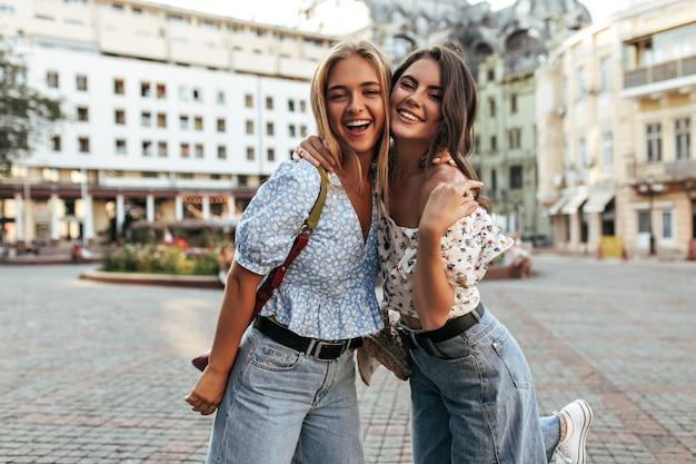 Jovens amigas em jeans elegantes e blusas florais da moda abraçam, sorriem e posam de bom humor na praça da cidade