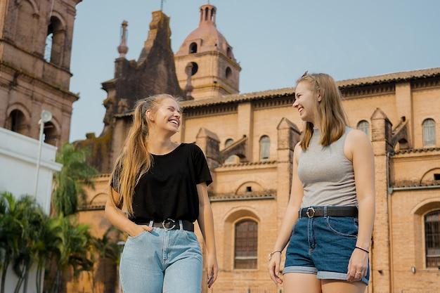 Jovens amigas em pé na parede da catedral de santa cruz de la sierra