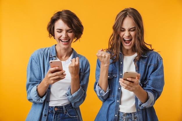 Jovens amigas empolgadas usando telefones celulares fazem gestos de vencedor.