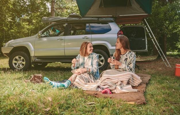 Jovens amigas felizes descansando sentadas sob um cobertor em um acampamento na floresta