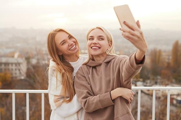 Jovens amigas felizes em roupas elegantes e aconchegantes, sorrindo e tirando uma selfie no smartphone enquanto estão no deck de observação na cidade durante o fim de semana juntos