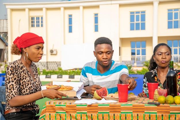 Jovens amigos africanos em um piquenique, comendo pizza, suco e frutas