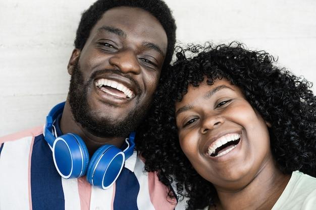 Jovens amigos africanos sorrindo para a câmera ao ar livre - foco nos rostos
