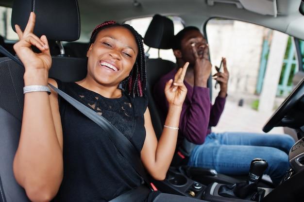 Jovens amigos afro-americanos, sentado dentro de um carro