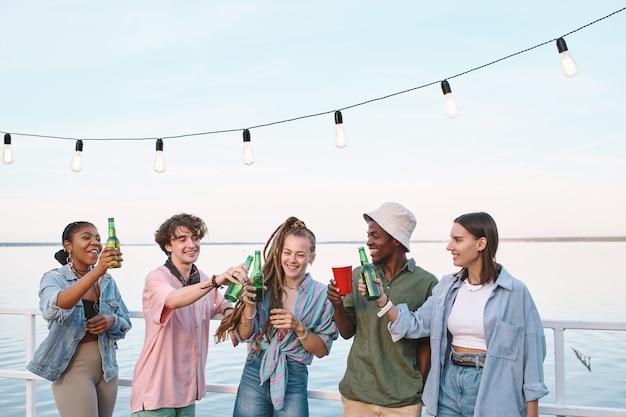 Jovens amigos alegres brindando com bebidas em festa ao ar livre