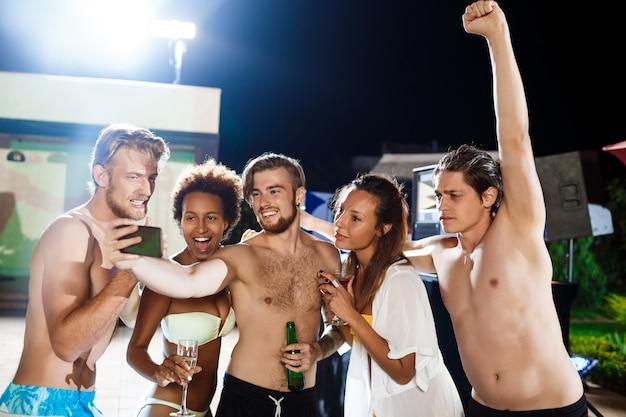 Jovens amigos alegres sorrindo, regozijando-se, fazendo selfie, descansando na festa