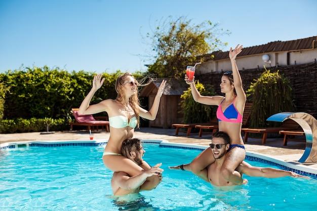 Jovens amigos alegres sorrindo, rindo, relaxando, nadando na piscina