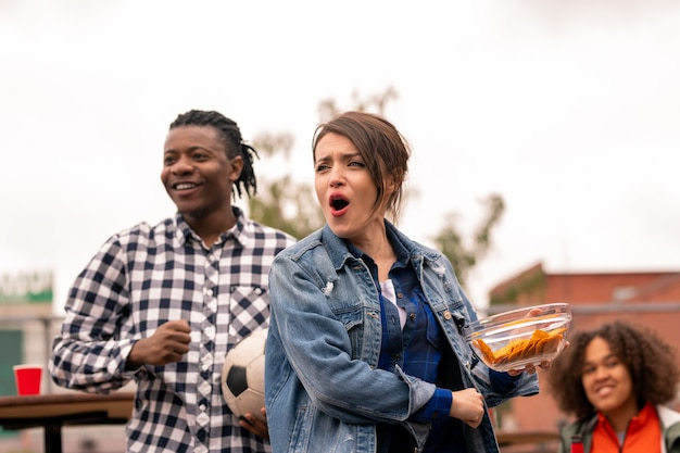Jovens amigos animados ou encontros em trajes casuais fazendo um lanche enquanto torcem por seu time de futebol durante a transmissão