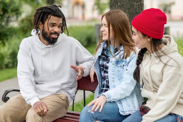 Jovens amigos ao ar livre no banco