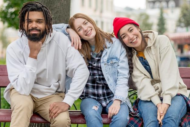 Jovens amigos ao ar livre, sentado no banco