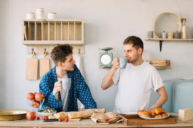 Jovens amigos, aproveitando a beber café com frutas e pães no balcão da cozinha