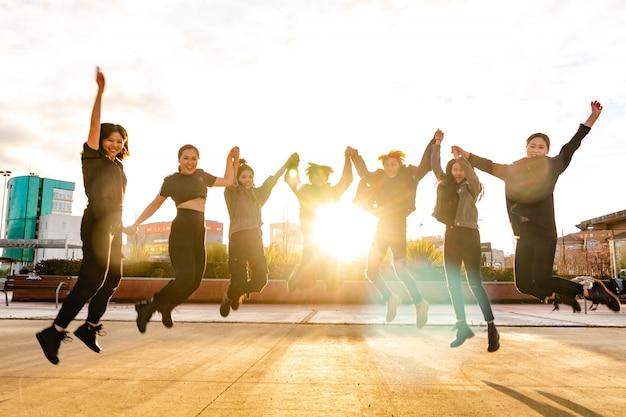 Jovens amigos asiáticos pulando ao pôr do sol. equipe chinesa vencedora