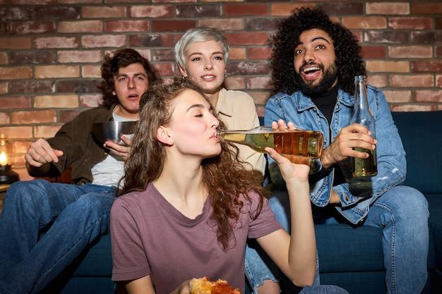 Jovens amigos assistindo tv, programa de comédia ou filme, comendo lanches e bebendo bebidas, sentados no sofá aconchegante em casa, diversos rapazes e moças aproveitando o tempo livre, o fim de semana juntos