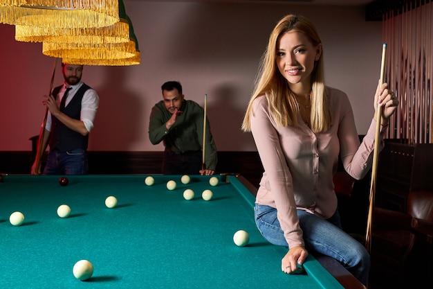 Jovens amigos ativos jogam bilhar no bar depois do trabalho, têm tempo de descanso e folga, preparando-se para atirar bolas de bilhar