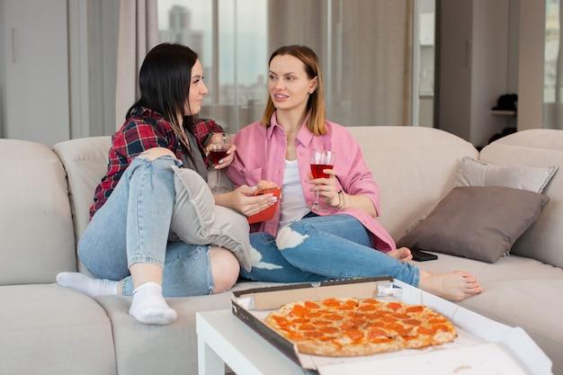 Jovens amigos bebem vinho comem pizza de calabresa e conversam bem sentados no sofá o conceito de uma vida feliz foto de alta qualidade