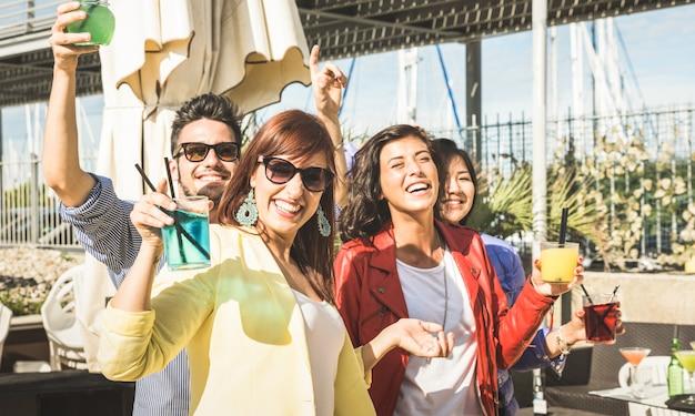 Jovens amigos bebendo e dançando na festa ao ar livre