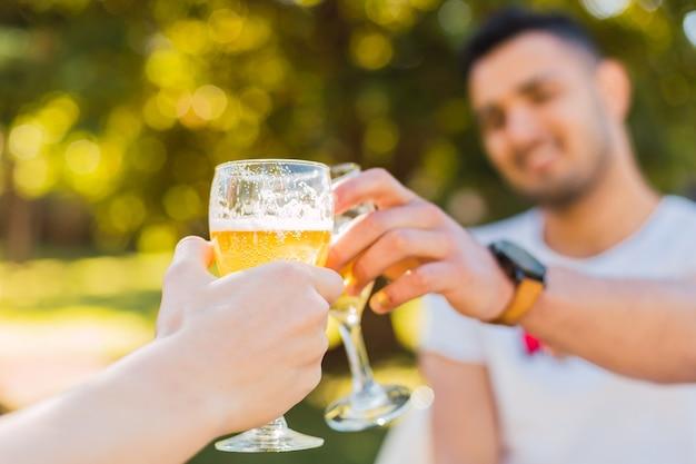 Jovens amigos brindam com cerveja.