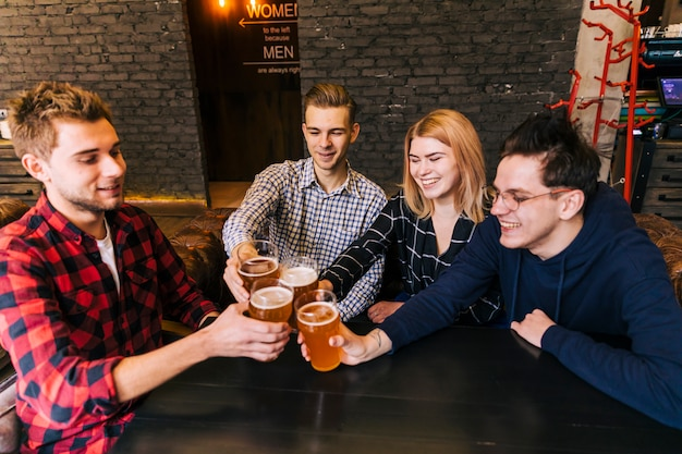 Jovens amigos brindando e tinindo com copos de cerveja no bar