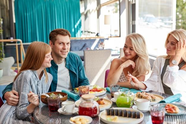Jovens amigos caucasianos felizes reunidos em um café