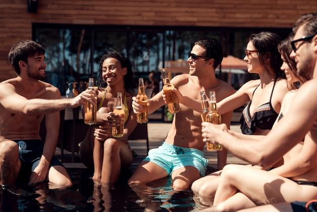 Jovens amigos com bebidas alcoólicas à beira da piscina