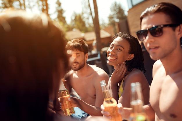 Jovens amigos com bebidas alcoólicas na piscina.