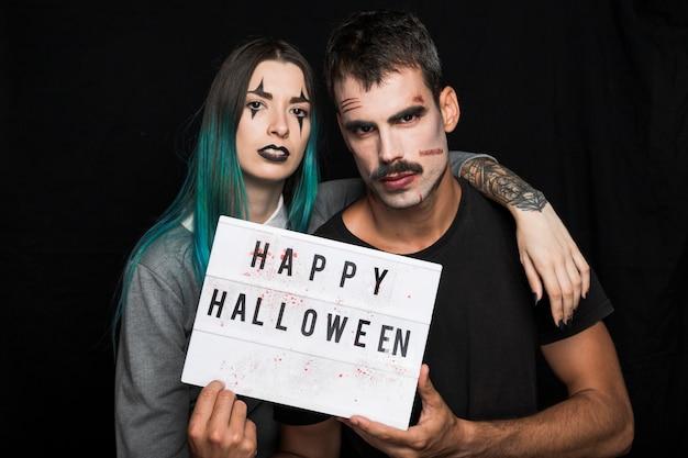 Jovens amigos com maquiagem de halloween segurando a tabuleta