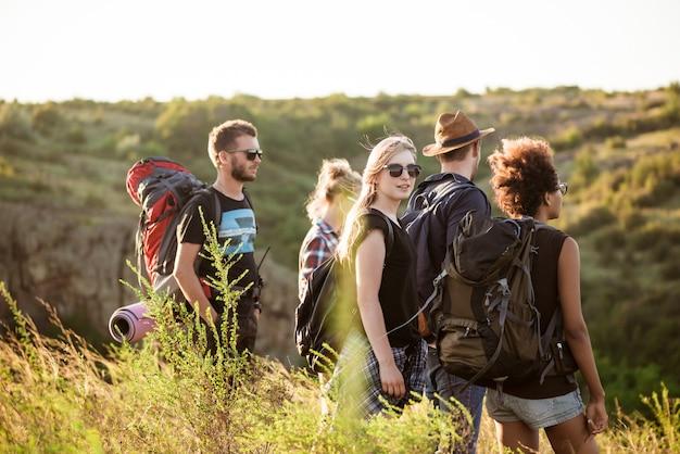 Jovens amigos com mochilas, apreciando a vista, viajando no canyon