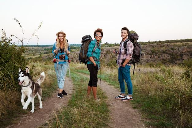 Jovens amigos com mochilas e huskies sorrindo, viajando no canyon