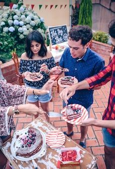 Jovens amigos comendo bolo e se divertindo em uma festa ao ar livre de verão